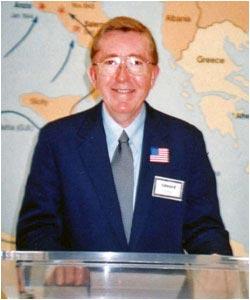 Ed Gordon speaking in front of European map